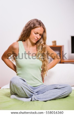 Young woman is sitting in her bed with pain in her back.