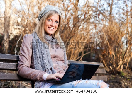 Young woman is sitting in park and using laptop. - stock photo