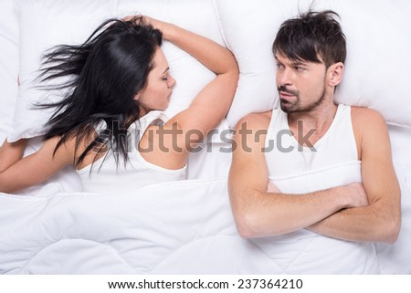 Young woman is sleeping in the bed. Husband is looking at her.