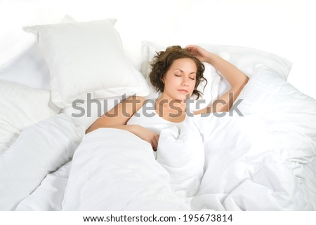 Young woman is sleeping on white linen, isolated on white background