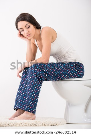 Young woman is sleeping while sits in a toilet. - stock photo