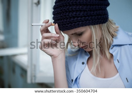 Young woman is smoking cigarette of marijuana. She is standing near the window. The drug addict closed eyes with depression - stock photo