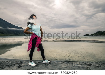 Young woman is smoking the vape on the beach of Norway