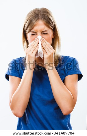 Young woman is sneezing into handkerchief.Woman having flu - stock photo
