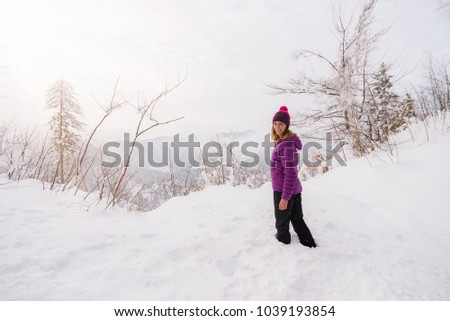 Young woman is standing in  deep snow dressed in colorful clothes and looking at the camera