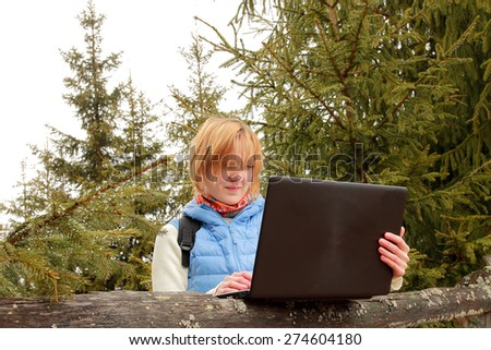 Young woman is standing through fir-trees and watching something in her laptop. - stock photo