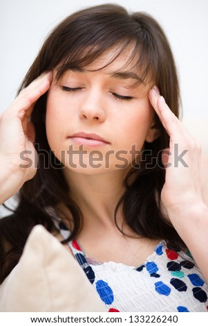 Young woman is suffering headache - stock photo