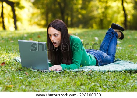 Young woman is surprised about something she had seen on her laptop,Surprised woman - stock photo