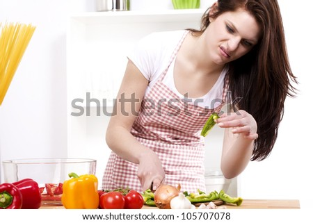 young woman is suspicious about the paprika she was chopping - stock photo