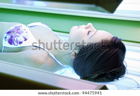 Young woman is tanning in solarium.