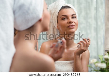 Young woman is trying her new fragrance - stock photo