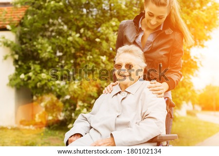Young woman is visiting her grandmother in nursing home having a walk with here in a wheelchair - stock photo