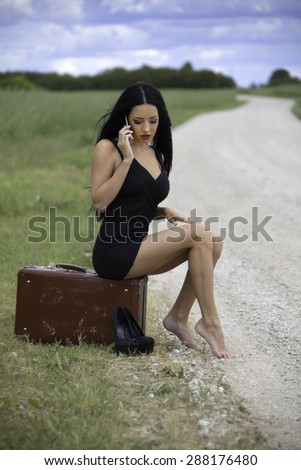young woman is waiting car on village road and talking by mobile phone - stock photo