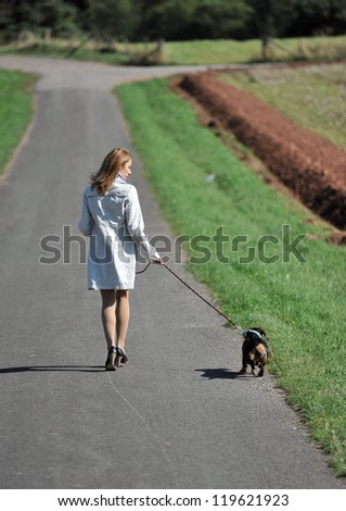 Young woman is walking with her small dog.