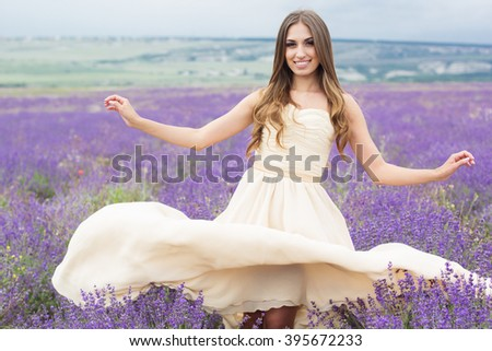 Young woman is wearing nice white dress walking at field of purple lavender flowers