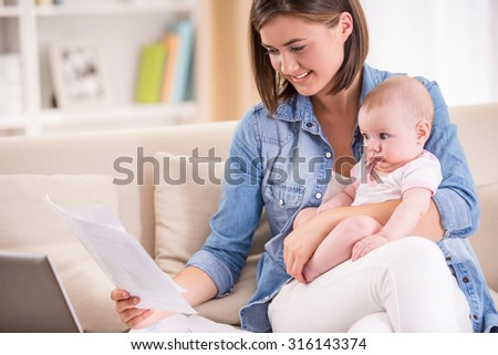 Young woman is working from home, holding baby girl on lap. - stock photo