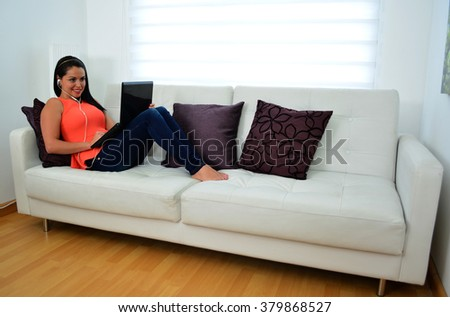 Young woman is working on a laptop in her living room.