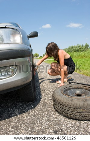 Young woman jacking up her car to change a flat tire with a spare one - stock photo