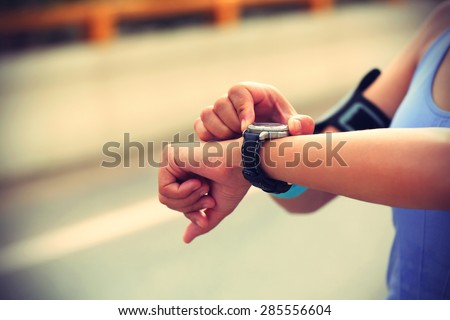young woman jogger ready to run set and looking at sports smart watch, checking performance or heart rate pulse trace. Sport and fitness outdoors in city. - stock photo
