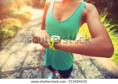 young woman jogger ready to run set and looking at sports smart watch, checking performance or heart rate pulse trace. Sport and fitness outdoors on forest trail. - stock photo