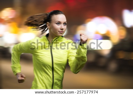 Young woman jogging at night in the city - stock photo