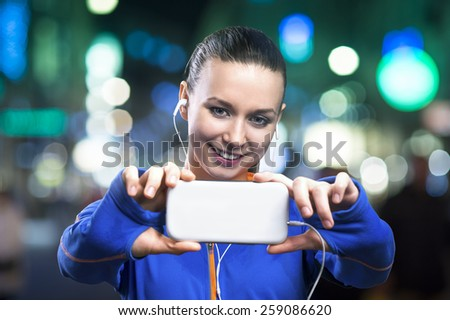Young woman jogging at night in the city taking selfie - stock photo
