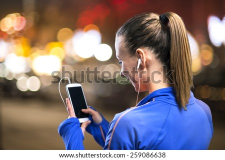 Young woman jogging at night in the city while listening music - stock photo