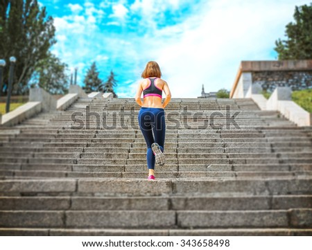 Young woman jogging at stairs outdoors - stock photo