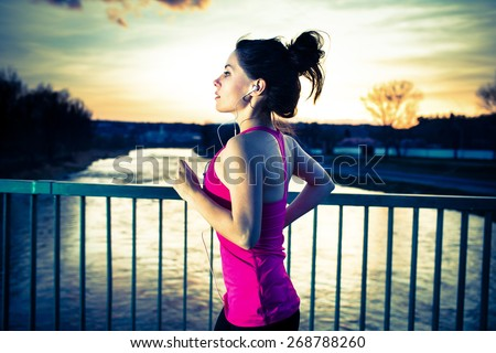 Young woman jogging at sunset in the city on the bridge cross the river. Girl running outdoors in a city park. Cross Process. Vintage filtered. - stock photo