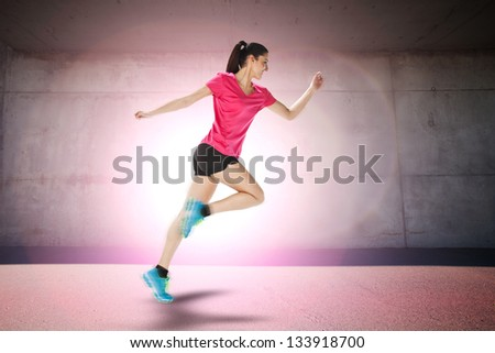 young woman jogging front cement wall. Sport woman starting running - stock photo