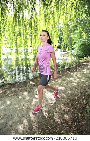 young woman jogging in a park or forest