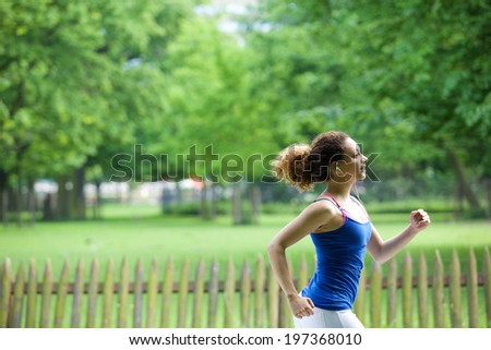 Young woman jogging in the park with earphones - stock photo