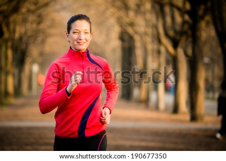 Young woman jogging in tree alley - early spring - stock photo