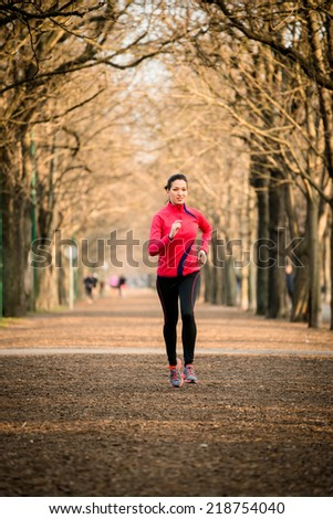 Young woman jogging in tree alley - late autumn - stock photo