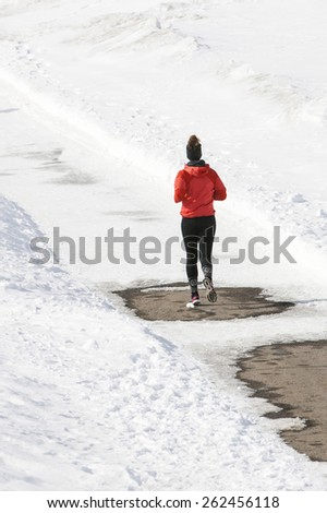 Young woman jogging in winter. - stock photo