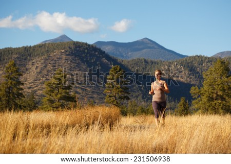 Young Woman Jogging on Beautiful Rural Outdoor Trail - stock photo