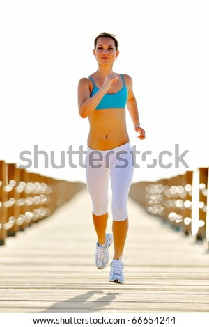young woman jogging on the beach - stock photo