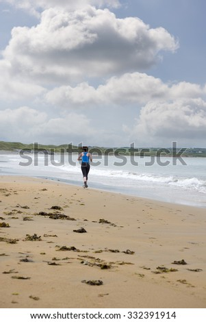 young woman jogging on the beach in ballybunion county kerry ireland - stock photo