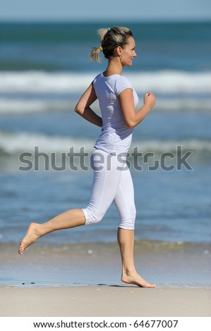 young woman jogging on the beach in summer