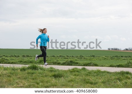 young woman jogging (running) outdoors - stock photo