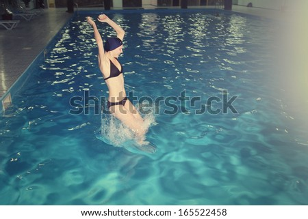 Young Woman jump in Pool - stock photo