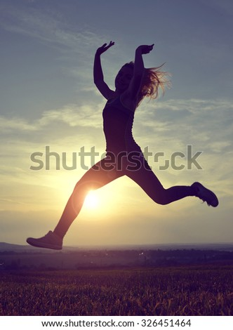 Young woman jumping at sunset