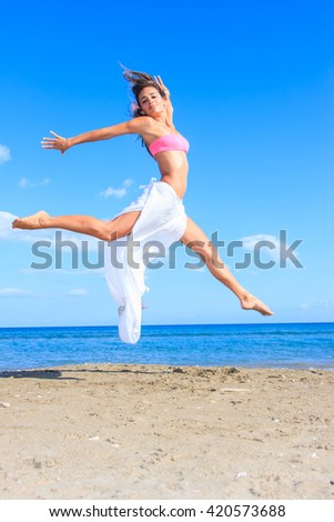 Young woman jumping at the beach.