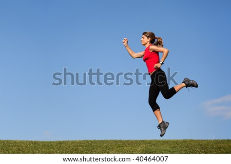 young woman jumping at the top of a hill