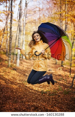 Young woman jumping during the rainy day at autumn   - stock photo