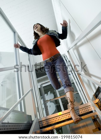 Young woman jumping from stairs - stock photo
