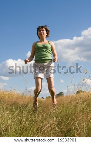 young woman jumping high on a summer day