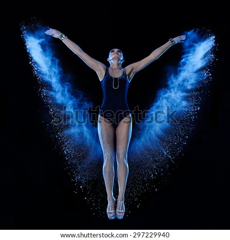 Young woman jumping in blue powder cloud on black background - stock photo