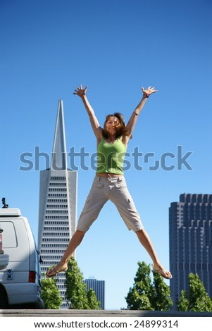 Young woman jumping in downtown San Francisco - stock photo