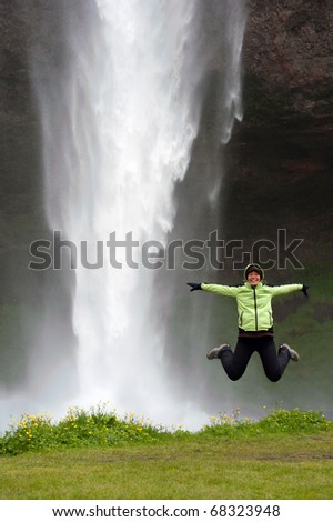 young woman jumping in front of Seljalandsfoss waterfall, Iceland - stock photo